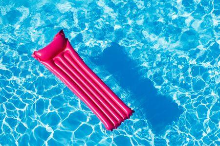 Materasso gonfiabile rosa che galleggia sulla superficie dell'acqua