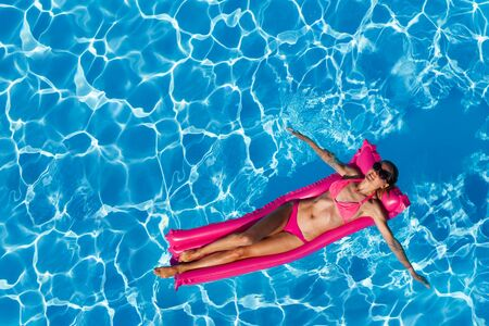 Woman floating on air mattress in swimming pool Stockfoto
