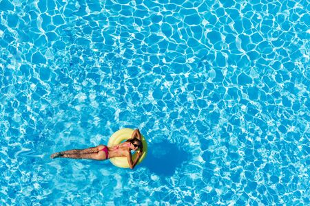 Niña feliz flotando en el anillo de aire en la piscina
