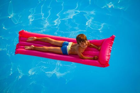 Smiling boy swimming on pink inflatable mattress Foto de archivo