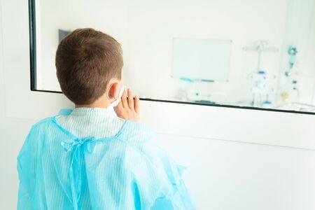 Little boy watching though hospital galls in ICU