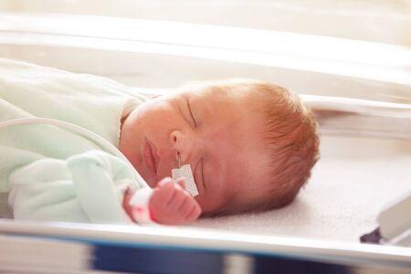 Close portrait of premature child with feeding milk through nose in ICU in hospital