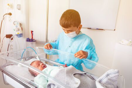 Baby brother and premature born infant child crib
