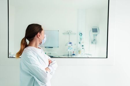 Doctor looking through hospital glass in ICU