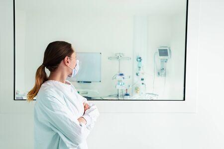 Doctor mirando a través del cristal del hospital en la UCI