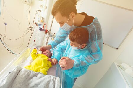 Father and brother with newborn child in ICU bed