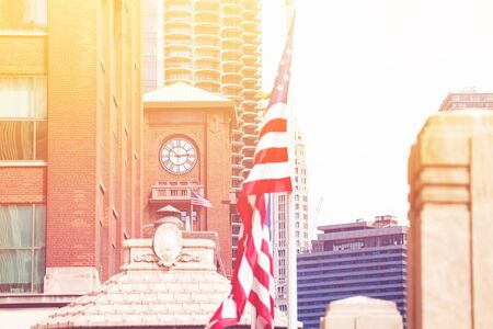 US flag over clocktower in downtown Chicago