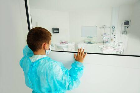 Little baby boy look through glass in ICU Stock Photo