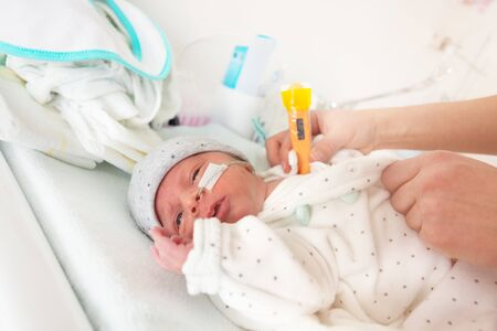 Premature born infant in ICU with thermometer