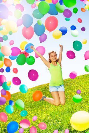La ragazza sorridente salta e tiene molti palloni ad aria