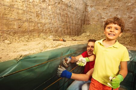 Little boy with father make concrete cellar walls Stock Photo