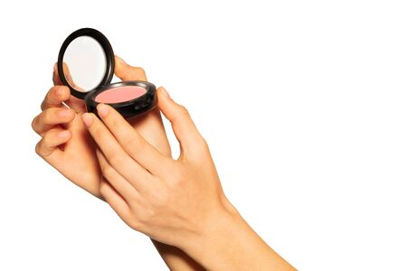 Womans hands holding opened blusher case on white