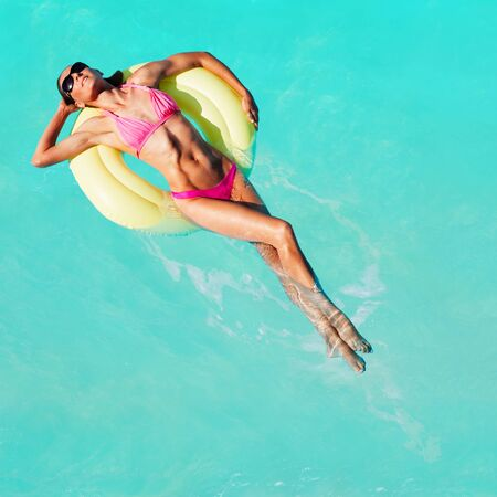 Women swim on yellow color buoys in the pool