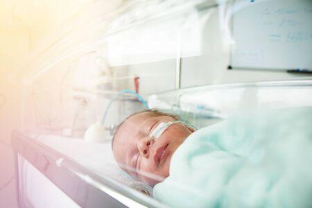 Pequeño niño prematuro a través de la cuna del hospital Foto de archivo