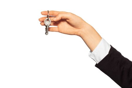 Womans hand holding metal door keys on the ring