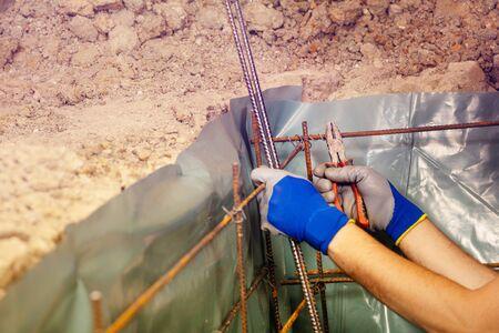 Nahaufnahme des Mannes, der Metallstangen für Beton strickt