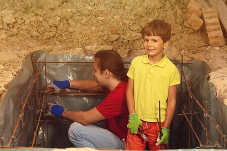 Little boy helps father to knit metal framework
