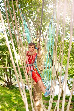 Walk from one tree to anther boy at adventure park Stock Photo