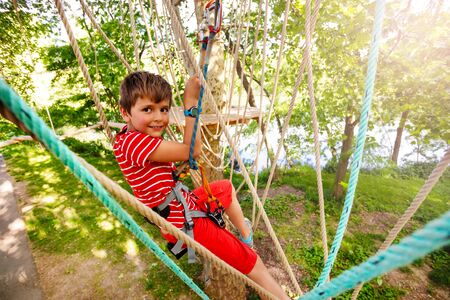 Happy boy pass ropes exercise at adventure park Stockfoto