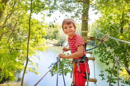 Happy boy on tree rope bridge in adventure park Standard-Bild