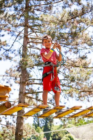 Little boy on suspended tree bridge at rope park Banco de Imagens