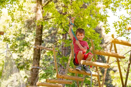 Boy portrait on sky rope suspended tree bridge Banco de Imagens - 128655543