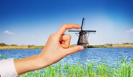 Female hand holding Kinderdijk windmill from afar