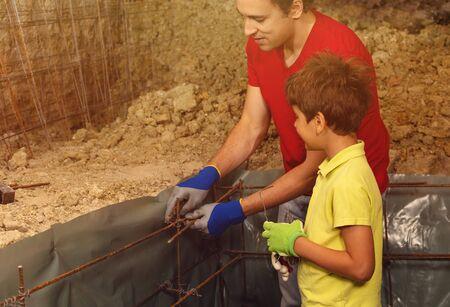 Father teaches boy prepare framework for concrete Фото со стока