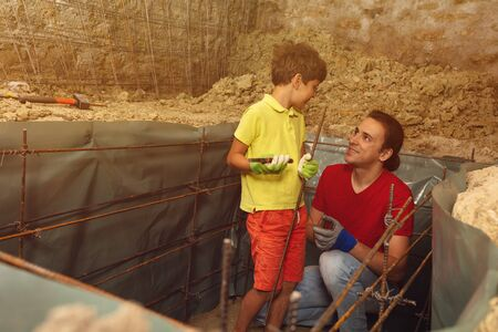 Father explain to little boy knitting metal rods