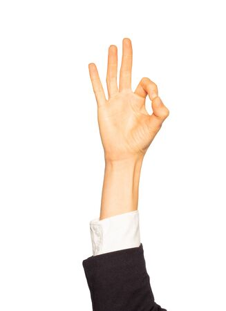 Female hand in business suit giving Okay gesture