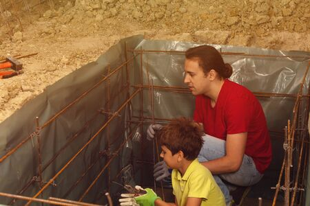 Father teaches son to knit metal rods for concrete