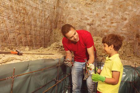 Boy help father make concrete cellar basement