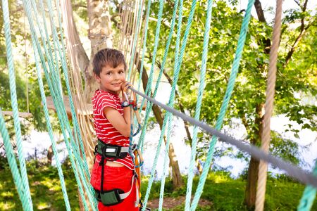 Boy walking on the ropes at adventure summer camp