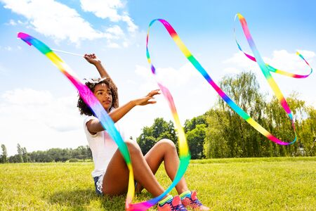 Girl wave long colorful ribbon sitting in park