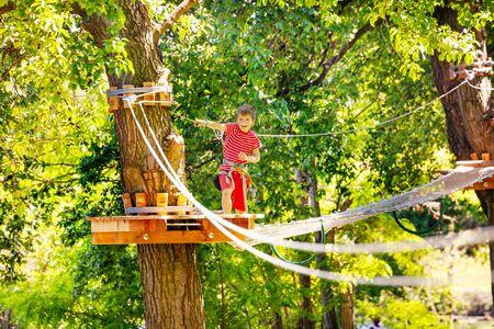 Junge übergibt Linie und Hängebrücke im Seilpark