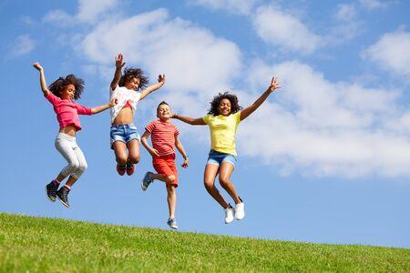 Groupe quatre enfants sautant au-dessus du ciel bleu