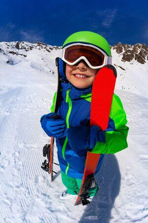 Boy hug ski and look up wearing mask with helmet Stock fotó