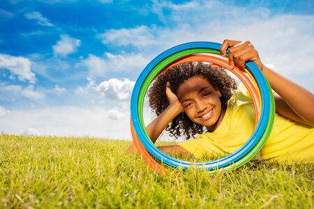 Happy young black girl looking through color hoops Banque d'images - 129574942