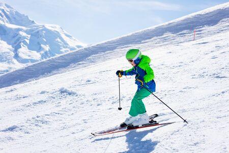 Pequeño esquiador montando cuesta abajo en alta montaña