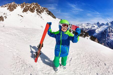 Fröhlicher Junge hält Ski mit Smartphone fotografieren Standard-Bild