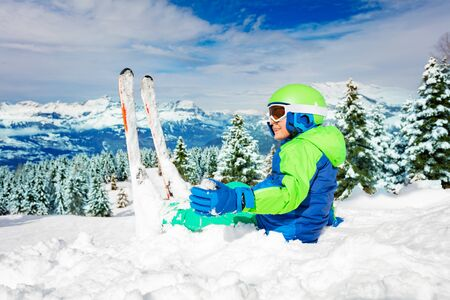 Boy rest in snow during ski over snowy forest