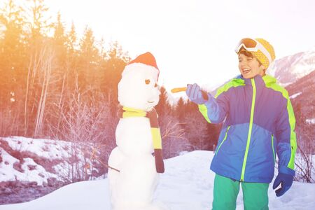 Boy laugh and put carrot to freshly made snowman Stockfoto