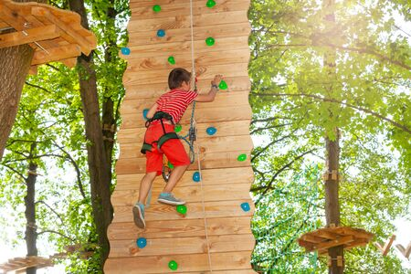 Boy rock climb high in the rope adventure park
