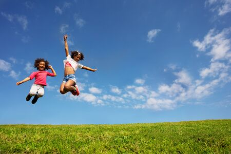 Two happy girls jump high over blue sky on lawn