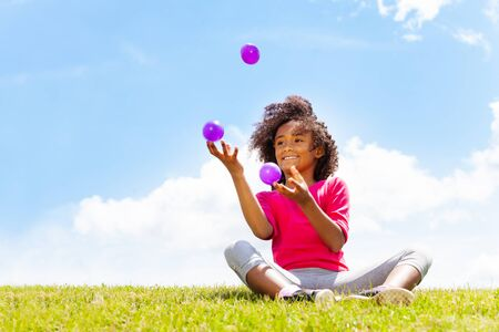 Fille heureuse positive jongler avec des balles sur l'herbe