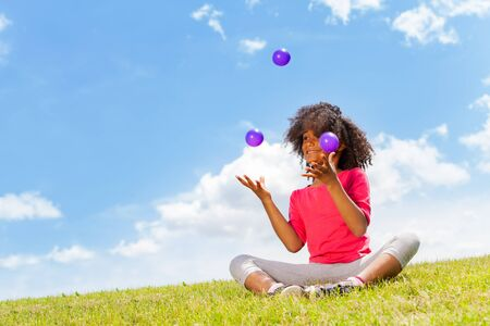 Beautiful little girl juggle with balls on lawn Banque d'images
