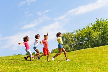 Widok z boku biegnącej grupy dzieci na trawniku w parku