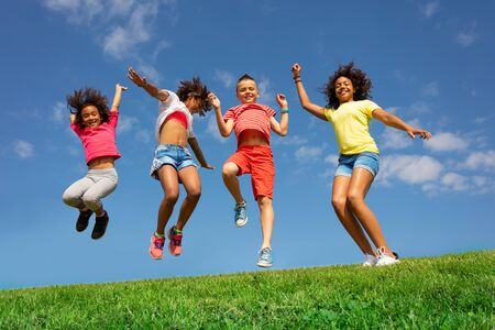 Dancing and jumping group of diverse kids on lawn Stock Photo