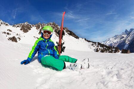 Glücklicher lächelnder Junge sitzt mit Ski auf der Piste