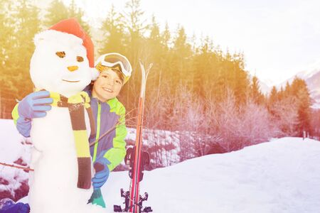 Portrait of the boy hug snowman and hold ski